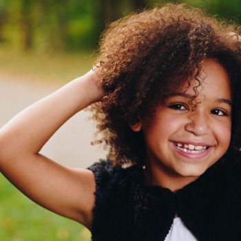 Smiling girl with curly brown hair
